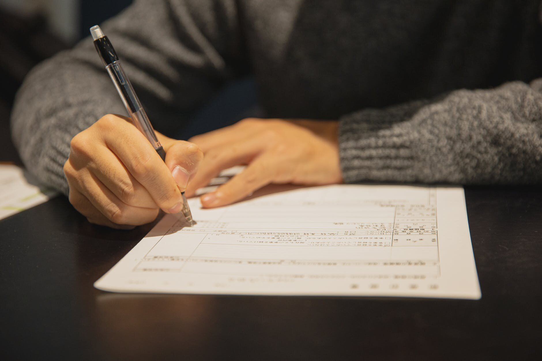 man filling in form on parer at table